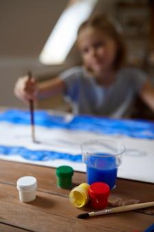 Детский рисунок с кистью и красками за столом, вид сверху, ребенок в мастерской. урок в художественной школе. молодой художник, приятное хобби, счастливое детство