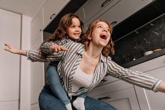女児は母親と遊んだり、笑顔を楽しんだりしています。キッチンで楽しんでいる女性と娘。