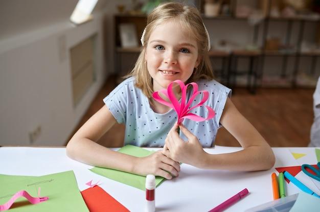 Ребенок женского пола клеит цветную бумагу за столом