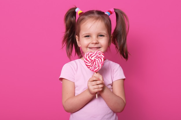 Female child holds huge striped lollipop in shape of heart, looks happy and excited, wears rose t shirt , stands smiling isolated on pink. little girl likes sweet candy.