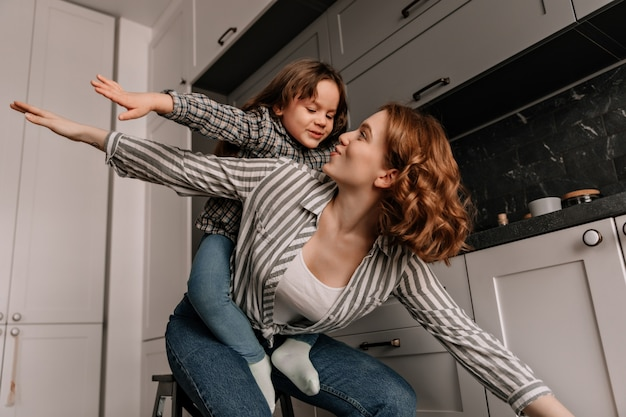 Female child sits at mothers back and plays with her like airplane in kitchen.