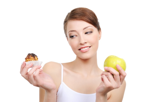 Female choice  high-calorie cake or healthy apple on white