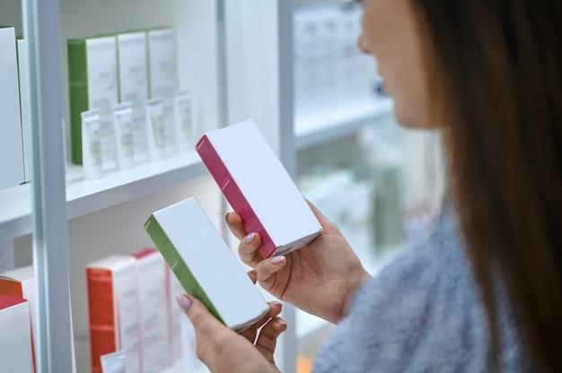 Женщина выбирает новые фармацевтические препараты в аптеке