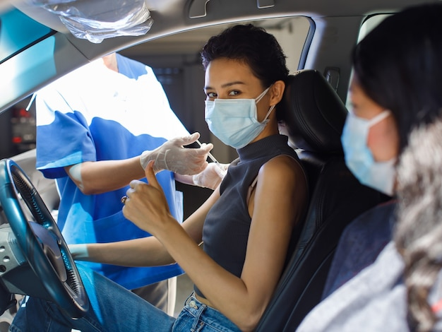 Female citizens wears face mask sitting look at camera in car with friend in drive through vaccinating line in hospital receiving coronavirus vaccine injection shot from public health doctor.