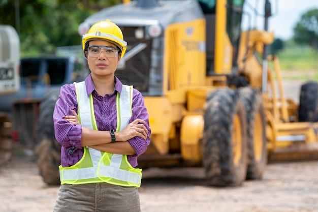 Женский инженер-строитель или архитектор с желтым шлемом, стоящим с бульдозером на строительной площадке.