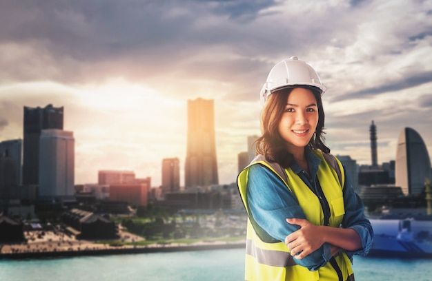 Female civil engineer with computer and blueprint is standing infront of japan yokohama skyscraper city for city development.
