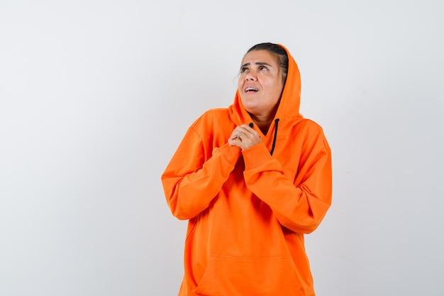 오렌지 까마귀에 가슴 위에 손을 쥐고 부끄러워하는 여성