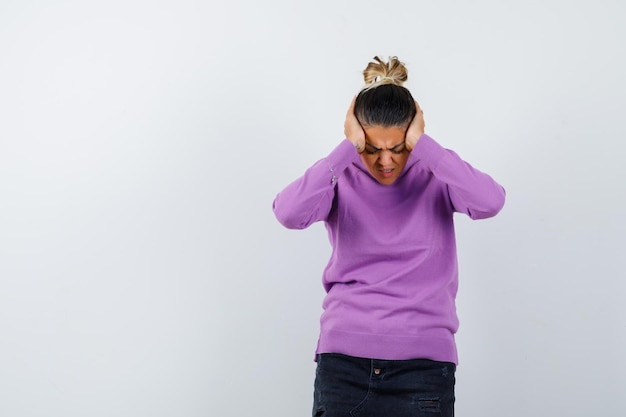 Femmina che stringe la testa con le mani in una camicetta di lana e sembra depressa