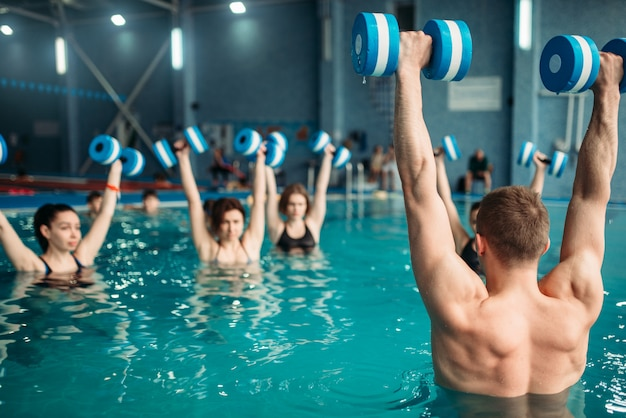 수영장에서 아쿠아 아령 운동에 트레이너와 함께 여성 클래스. 훈련, 수상 스포츠에 수영복을 입은 여성