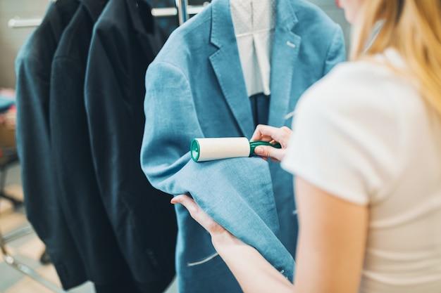 洗濯屋の女性クリーナーがきれいな服をチェックしていて、ローラーで糸くずを取り除いています。