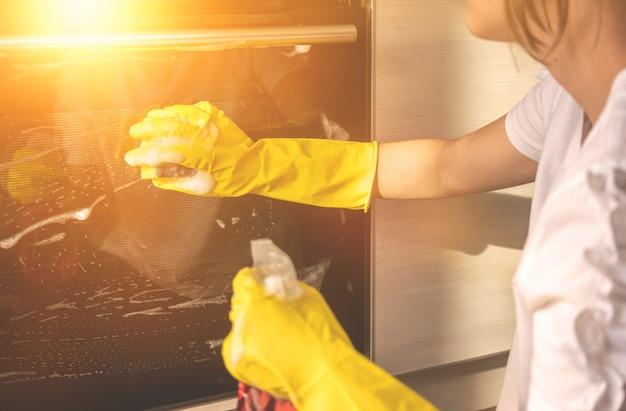 부엌에서 오븐을 청소하는 여성, 걸레와 스프레이 세제가 있는 노란색 고무 장갑에 손, 서비스 작업자 개념 배경 사진