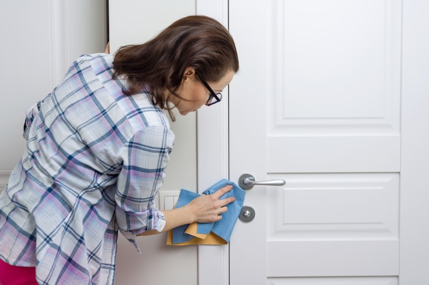 Female cleans a dirty door at home