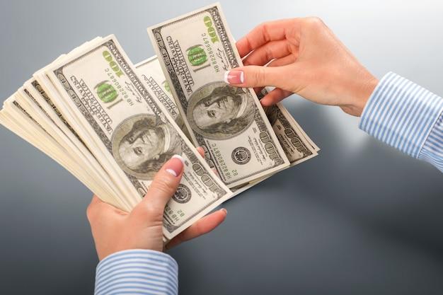 Женщина-клерк считает доллары. женские руки, считая долларовые банкноты. когда калькулятор сломан. надо делать это быстро.