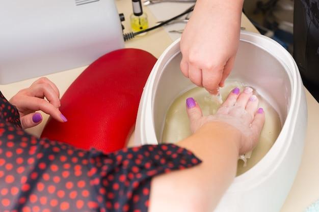파라핀 왁스 매니큐어 스파 치료 중 따뜻한 왁스 통에 손을 담그는 여성 클라이언트 - 높은 각도 보기 닫기