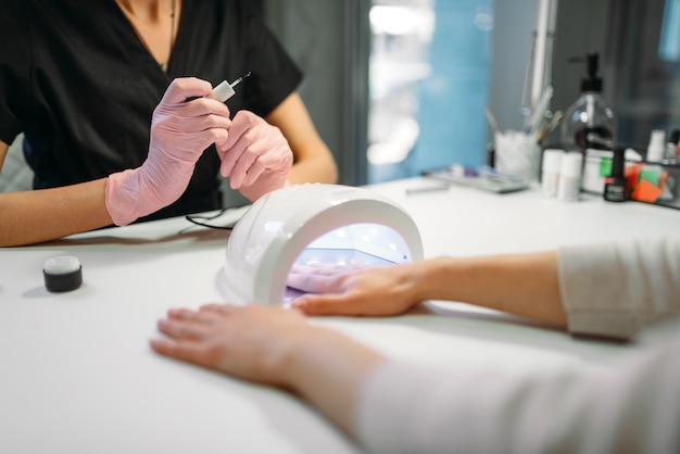 女性のお客様はネイルドライヤーでゲルニスを乾燥させます
