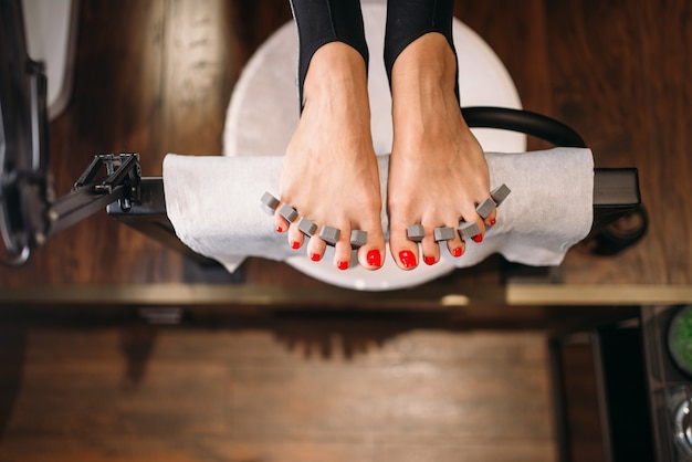 Female client foot, top view, pedicure cosmetic procedure in beauty salon