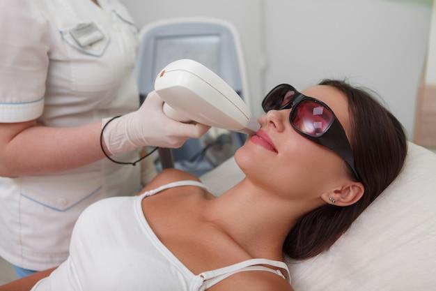 ビューティーサロンで顔の毛のレーザー脱毛を受ける女性のクライアント