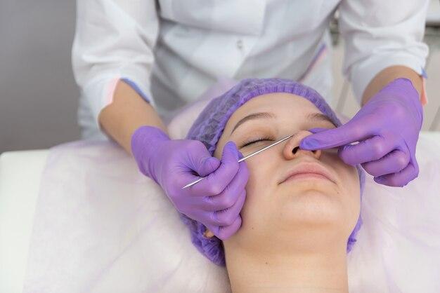 女性のクライアントは、アイループ美容とスキンケアルーチンの助けを借りてフェイシャルトリートメントを受けています