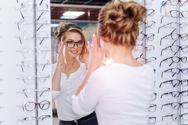 Female client, optician is standing with many glasses in background in optical shop. eyesight correction. woman wears dioptric. closeup.