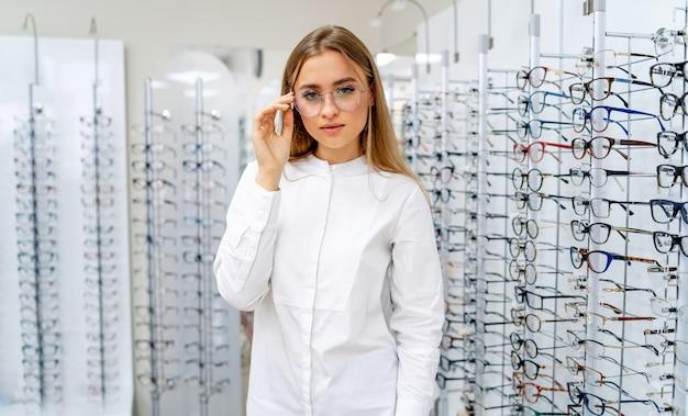 여성 고객 또는 안경점은 백그라운드에서 안경의 원시와 함께 서 있습니다.