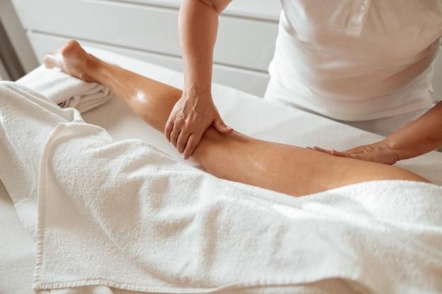 웰빙 센터에서 다리 마사지를 받는 여성 고객