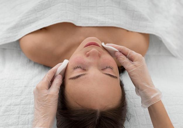 Cliente femminile al salone per routine di cura del viso con dischi detergenti