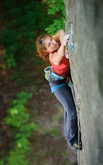 Female climber climbing steep rock, searching for next grip