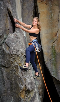 Female climber climbing with rope on a steep rocky wall