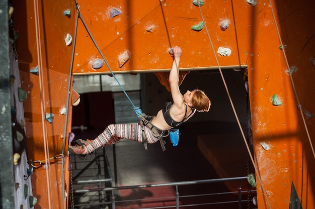 Female climber climbs on an indoor rock-climbing wall