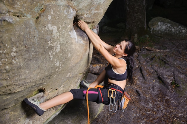 Female climber is starting her route on the natural rocky wall with rope