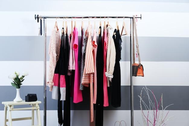 Женская одежда на вешалках в комнате