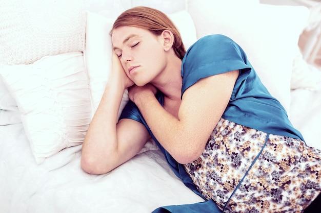 Женские скатерти. рыжий короткошерстный трансгендер спокойно спит на своей кровати в женской синей ночнушке