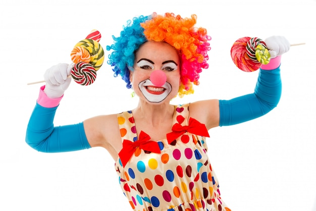 Female clown in colorful wig holding lollipops in both hands