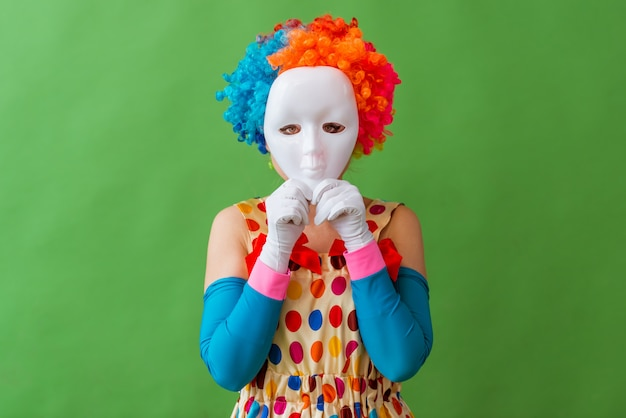 Female clown in colorful wig holding a mask on her face.