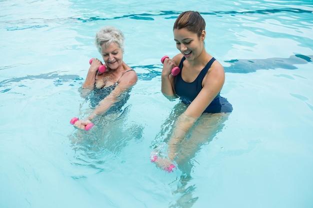 수영장에서 아령을 들기에서 고위 여자를 돕는 여성 코치