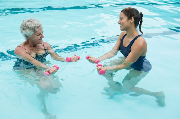 Female coach assisting senior woman in lifting dumbbells in swimming pool
