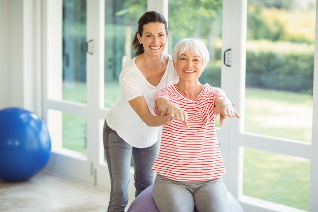 Female coach assisting senior woman in performing exercise