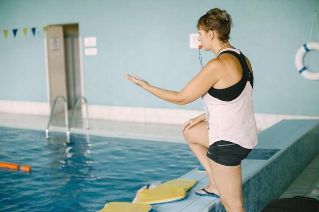 Женский тренер дает свисток. она советует пловцов. спортивная концепция.