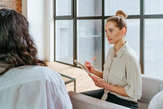 여성 코치는 실내 공책에 메모를 작성하는 연수생을 인터뷰합니다. 선택적 초점입니다.
