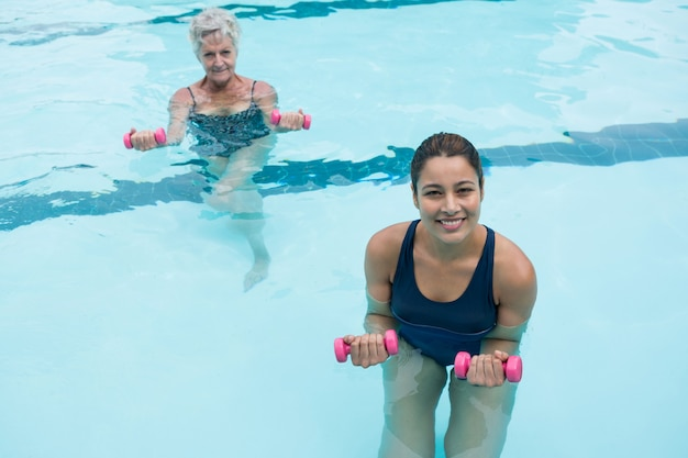 Female coach and senior woman exercising with dumbbells in swimming pool