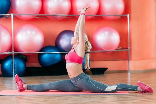 Female coach training split in gym