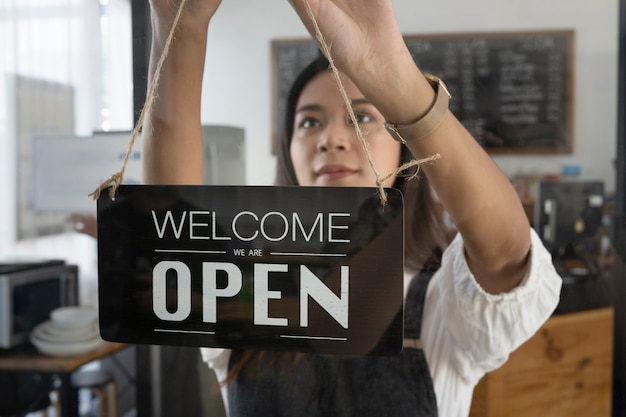 Владелец женского кафе, висит открытый знак на стеклянной двери.