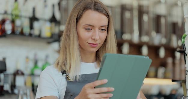 Владелец женского кафе, стоя перед прилавком, с помощью цифрового планшетного компьютера в современном кафетерии. женщина-официантка или бариста-работник кафе, держащего современное устройство.