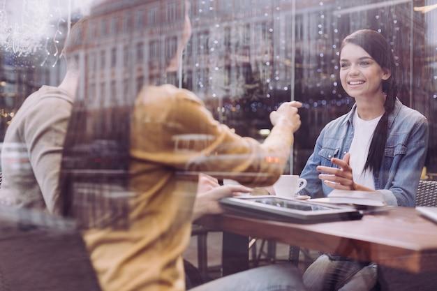 몸짓과 미소를 짓는 여성의 손가락으로 가리키는 여성 동료