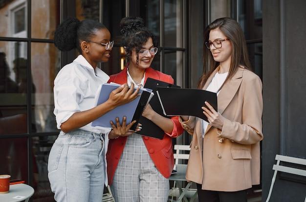 Colleghe che discutono i dati nella caffetteria all'aperto. donne multirazziali che analizzano la strategia produttiva per la proiezione aziendale utilizzando documenti in street cafe