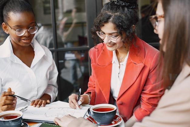 카페 야외에서 데이터를 논의하는 여성 동료. 거리 카페에서 문서를 사용하여 비즈니스 프로젝션을위한 생산적 전략을 분석하는 다인종 여성 명