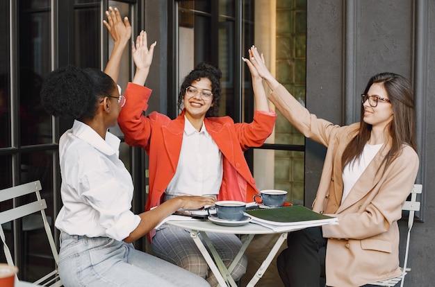 Коллеги обсуждают данные в кафе на открытом воздухе. многорасовые женщины анализируют продуктивную стратегию бизнес-проектирования с использованием документов в уличном кафе Premium Фотографии