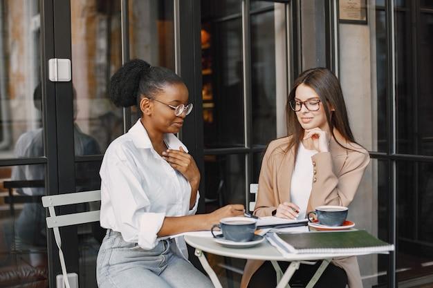 야외 카페에서 데이터를 논의하는 여성 동료. 거리 카페에서 문서를 사용하여 비즈니스 계획을 위한 생산적인 전략을 분석하는 다인종 여성