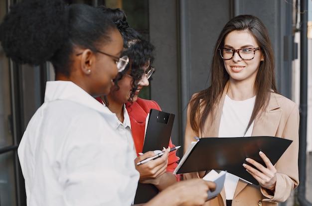 屋外のカフェでデータについて話し合う女性の同僚。ストリートカフェのドキュメントを使用してビジネスプロジェクトの生産戦略を分析する多民族の女性