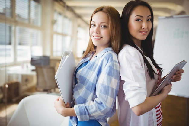 創造的なオフィスで背中合わせに立っている女性の同僚